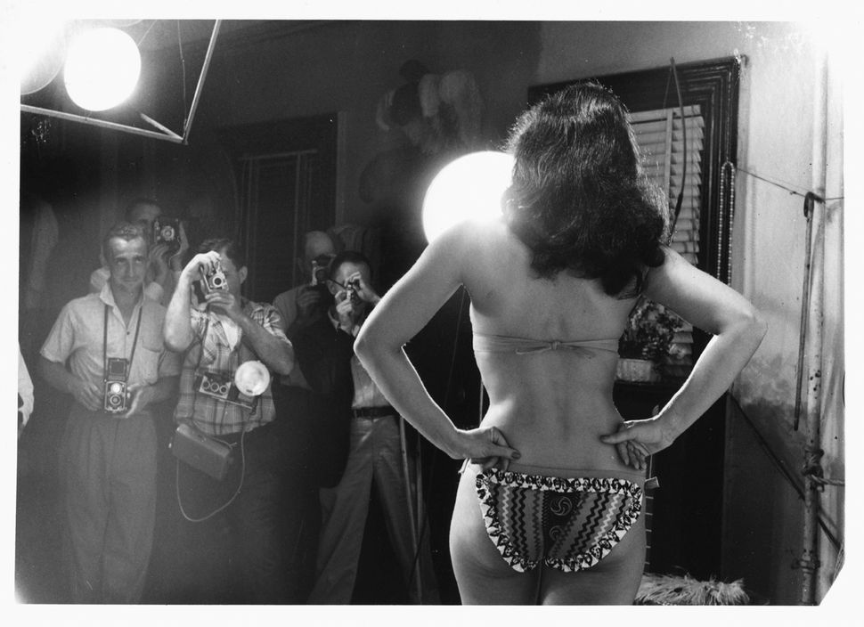 Dressed in a bikini, American pin-up model Bettie Page (1923 - 2008) poses with her hands on her hips as photographers take h
