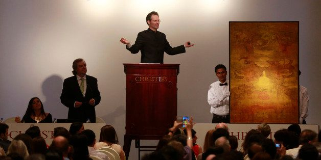 Christie's International Director, Asian Art, Hugo Weihe, center, acts as auctioneer for the painting of Indian artist Vasu