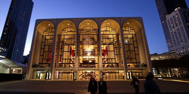 Pedestrians stroll at dusk in Josie Roberston Plaza near the Metropolitan Opera House in Lincoln Center, Wednesday, Nov. 13,
