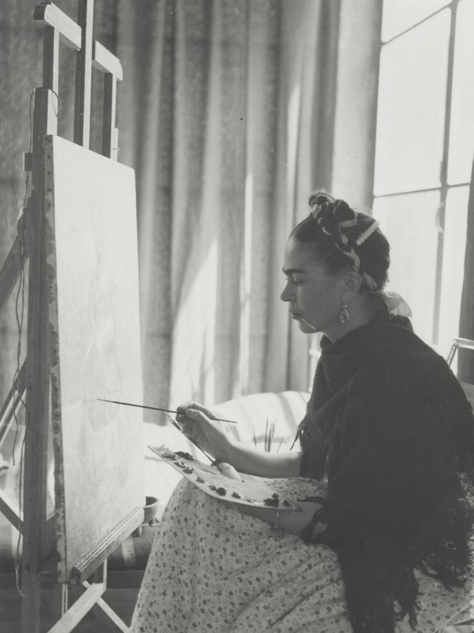 Hector Garcia image, Portrait of Frida Kahlo, in front of her painting of the Earth Goddess Frida Diego c1940 gelatin silver