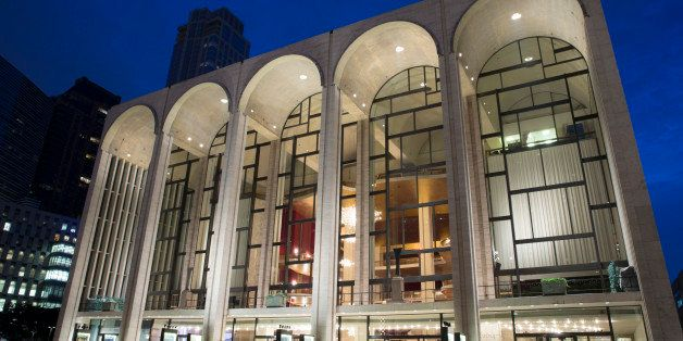 Pedestrians mill about the Metropolitan Opera house at Lincoln Center in the afterglow, Friday, Aug. 1, 2014, in New York. (A