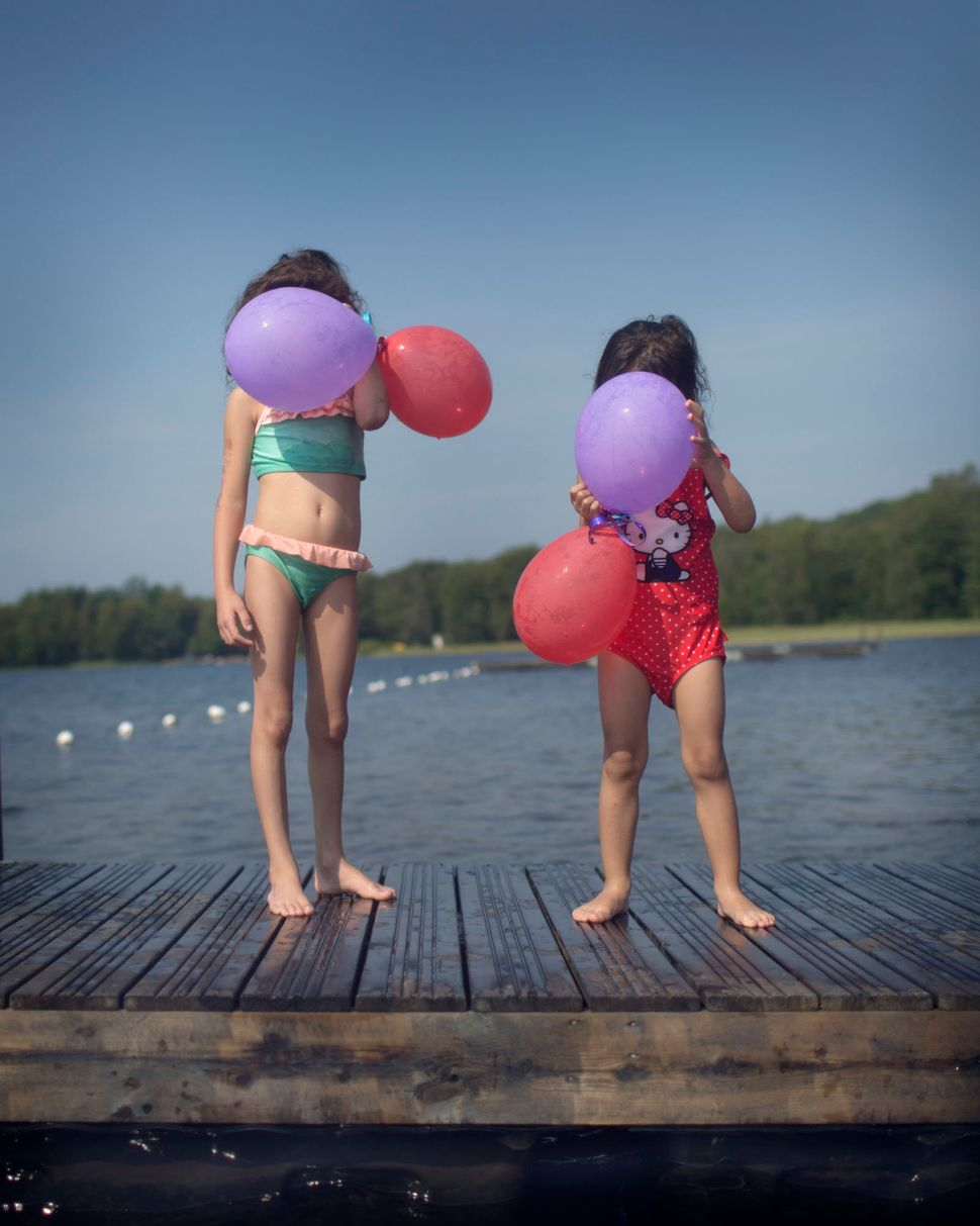 Some children swim in a lake for the first time. They can play and laugh, without being scared.