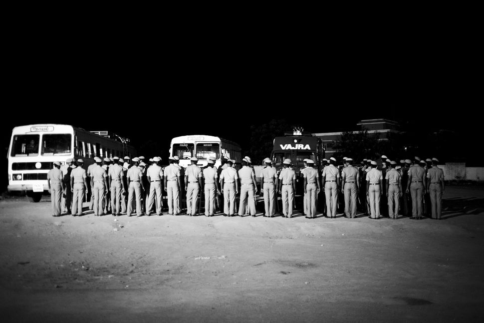 Police forces assemble in front of the KNPP, preparing to go on rounds in Koodankulam village after the imposition of a curfe