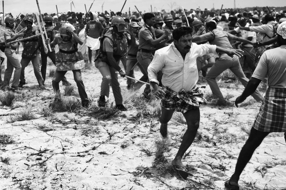 Napolean, a resident of Idinthakarai, runs after being attacked by the police.