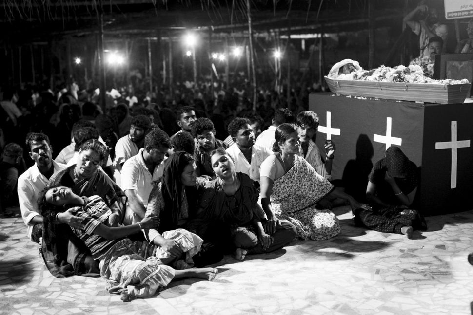 Children of Sahayam cry during his funeral mass. A low flying Indian Coast Guard plane startled him, causing him to fall off