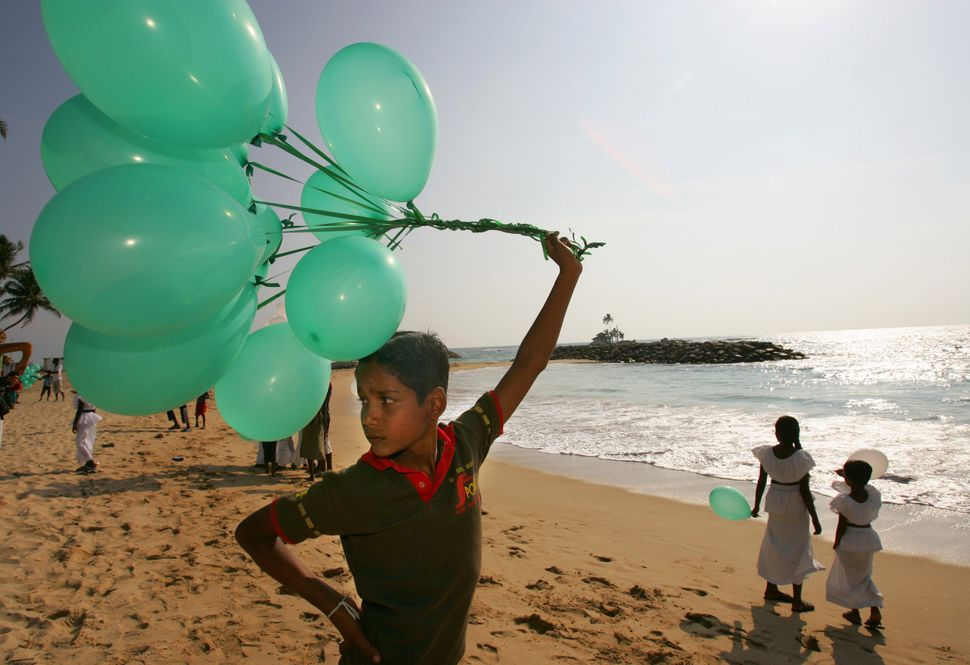A Sri Lankan boy holds balloons with other children before a balloon release to promote positive thinking about the water, sp