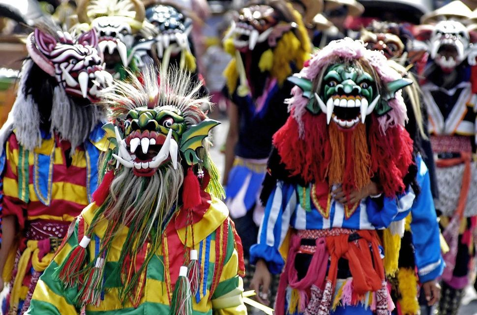 Participators who live on the slopes of the Mount Merapi volcano wear colorful outfits and masks during a parade in Yogyakart