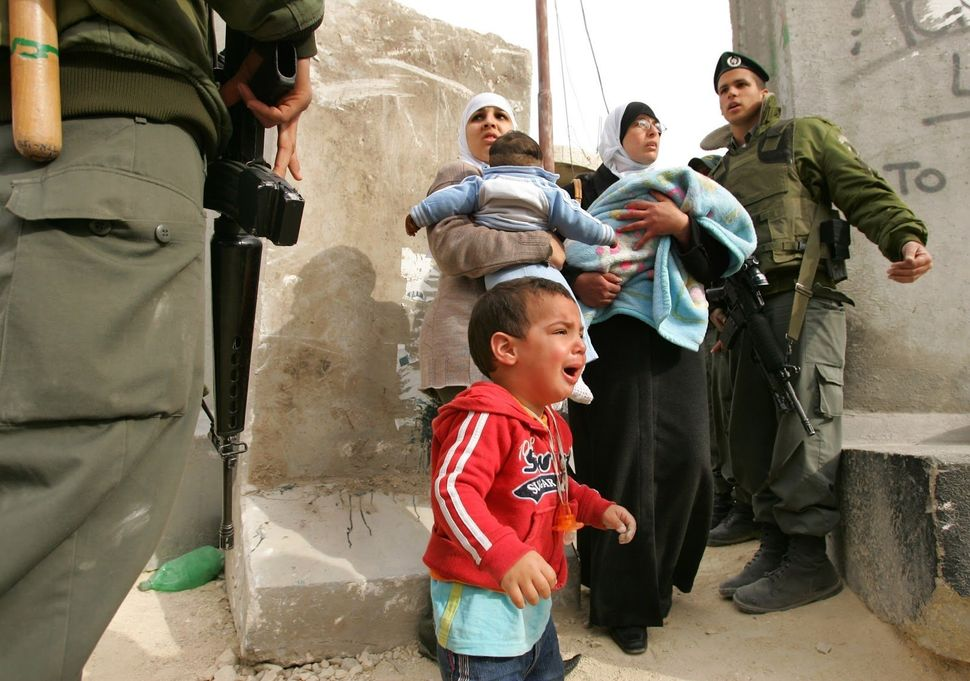 A child cries as Palestinian women argue with Israeli soldiers while they try to cross from Abu Dis into East Jerusalem on Ma