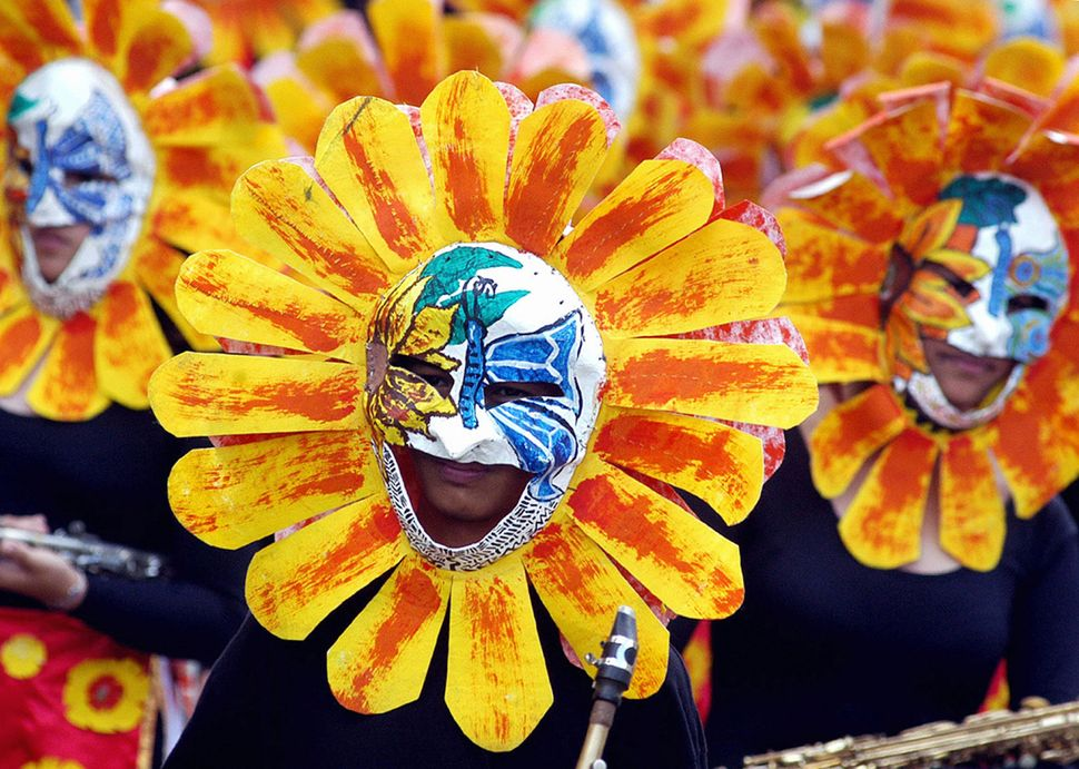 University students clad in colorful flower costumes dance in front of spectators during the celebration of the annual Panagb