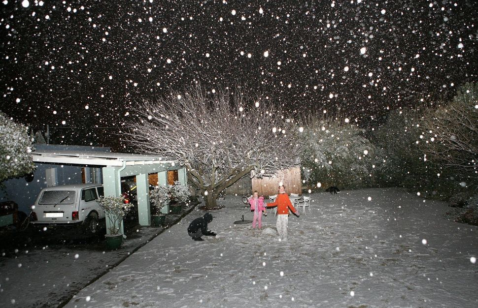 Children play in the snow in Johannesburg on June 27, 2007. The unexpected snowfall caused disruption in Johannesburg and sev