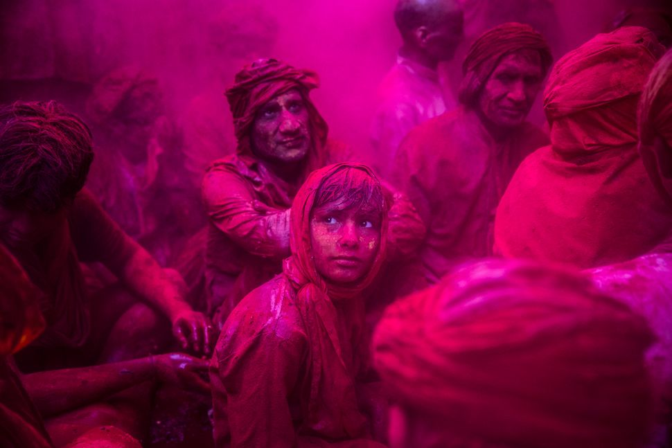 A boy looks on as Hindu devotees play with color during Lathmaar Holi celebrations on March 21, 2013, in the village of Barsa