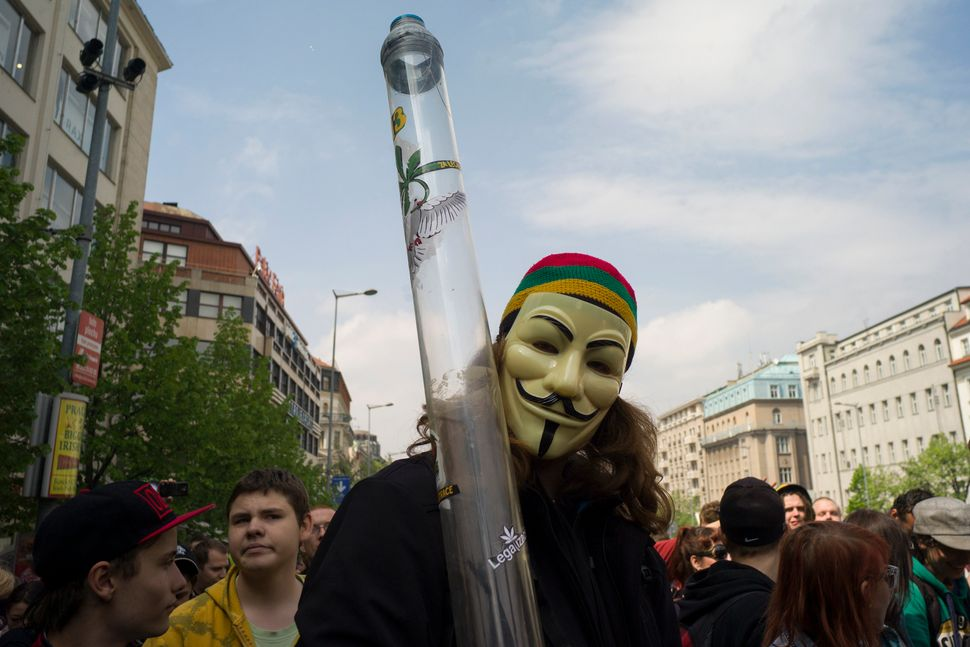 A masked man holds up a water pipe as people take part in a demonstration for the legalization of marijuana in the Czech Repu