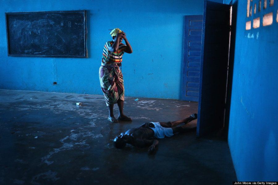 Omu Fereneh stands over her husband Ibrahim after he staggered and fell, knocking him unconscious in an Ebola ward on August