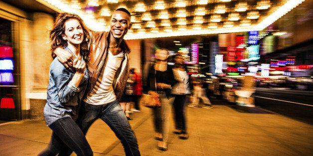 Couple having fun at night on Broadway, New York City.