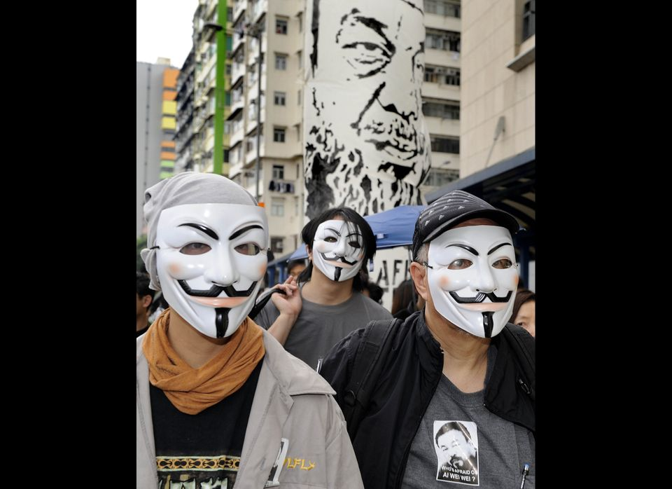 Protestors in Hong Kong's Tsim Sha Tsui district wear Guy Fawkes masks in protest of Ai's detention.