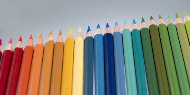 Colouring pencils in a row on a grey background.