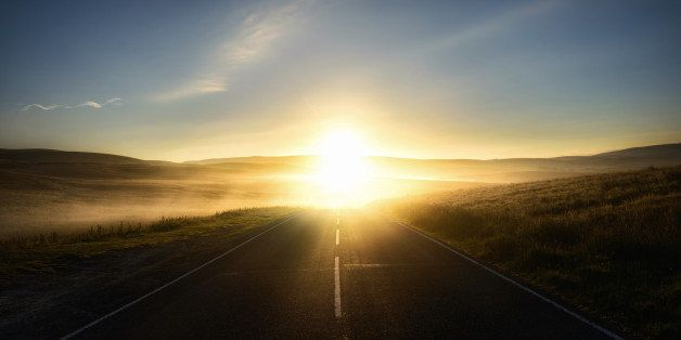 First sunlight reflecting from the mist on a road.