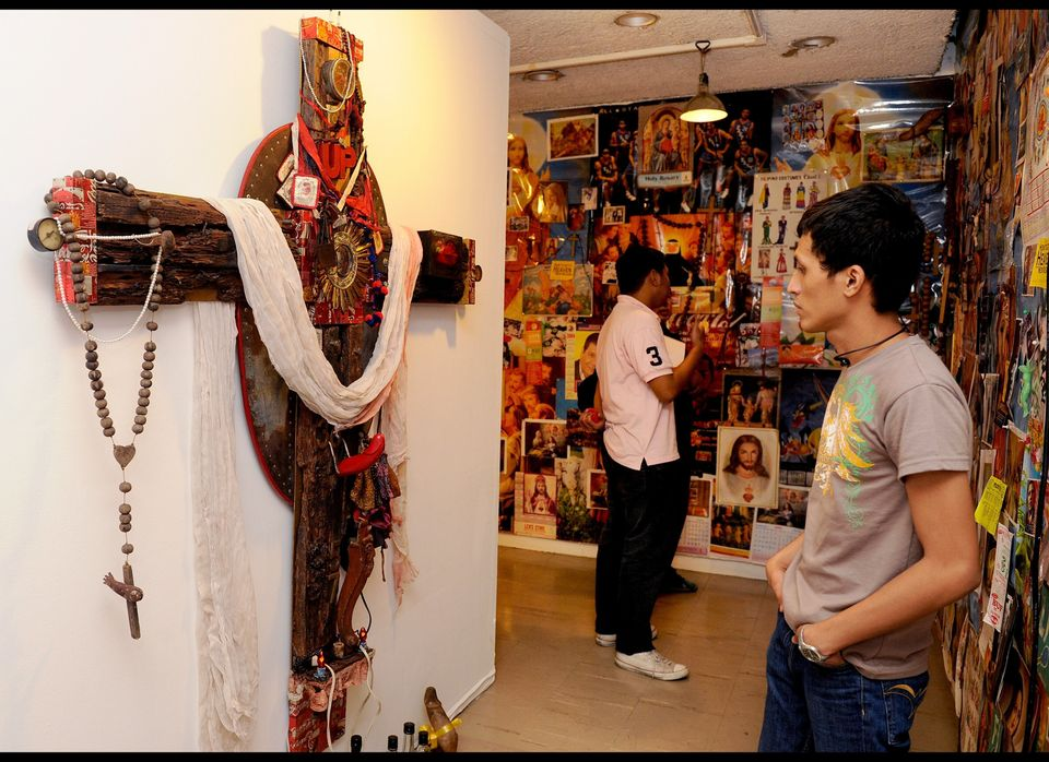 This photo taken on August 3, 2011 shows a student looking at artworks, which included a poster of Jesus Christ with a wooden