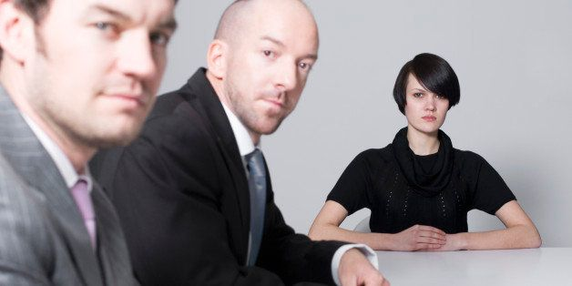 young woman sitting at conference table with two businessmen