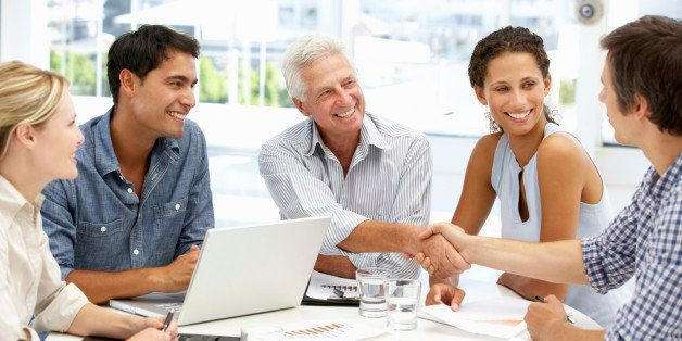 Mixed group in business meeting having a discussion shaking hands