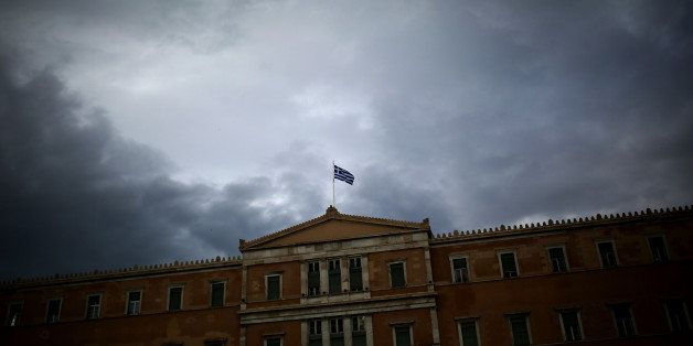 A Greek flag waves at the top of the Greek Parliament on May 22, 2016.  Greece on May 22, 2016 was set to adopt fresh cuts a