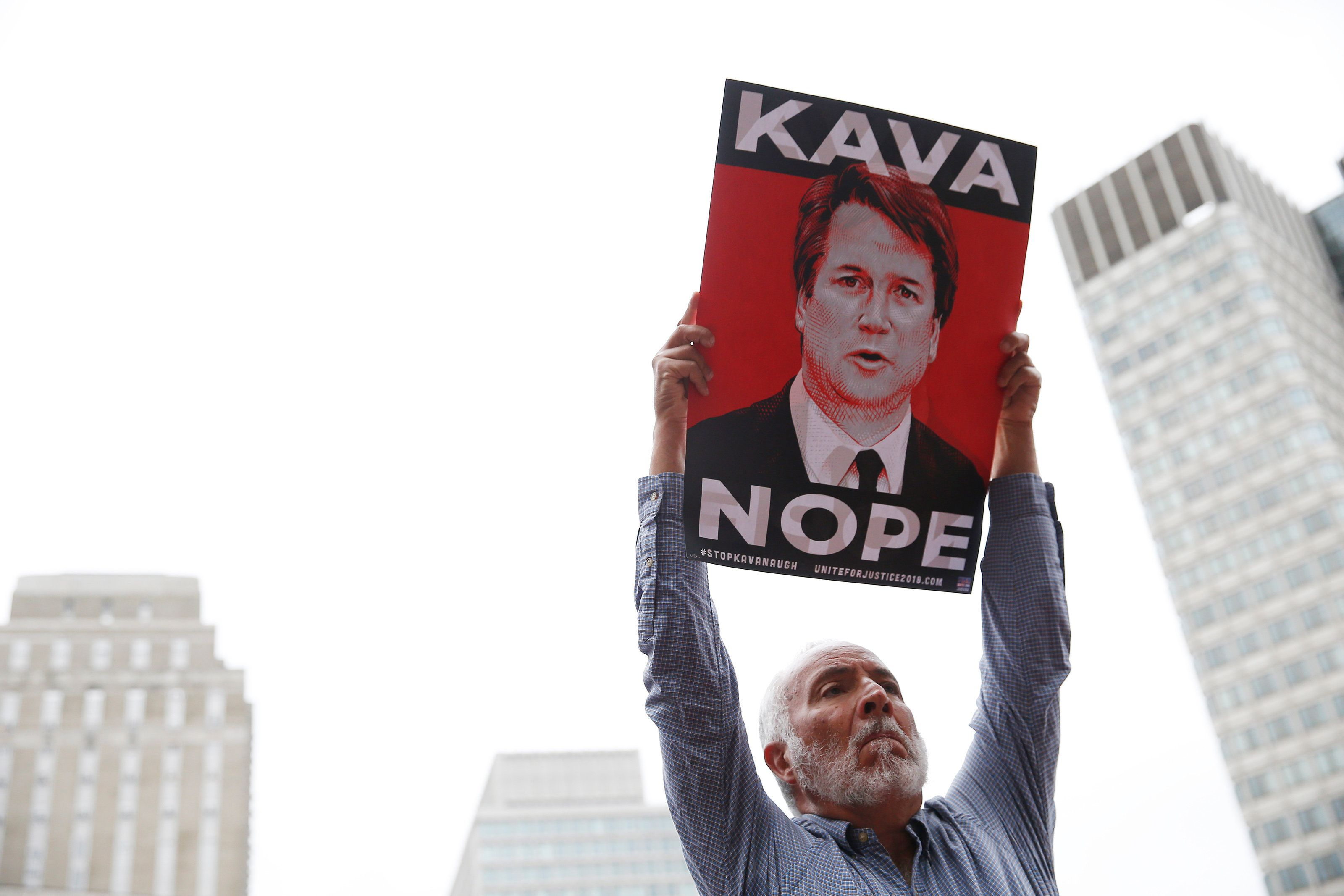 BOSTON, MA - OCTOBER 1: Gary Roden of Braintree holds a sign at a rally held to call on Senator Jeff Flake to reject Judge Brett Kavanaugh's nomination to the Supreme Court. The rally was held outside of City Hall in Boston ahead of Flake's appearance at Forbes Under 30 Summit on Oct. 1, 2018. (Photo by Jessica Rinaldi/The Boston Globe via Getty Images)