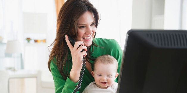 USA, New Jersey, Jersey City, Mother with baby daughter (6-11 months) working in home office