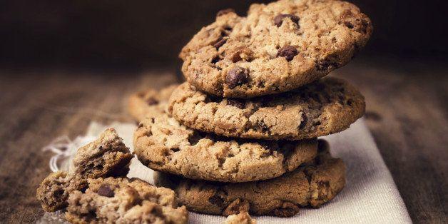 Chocolate chip cookies on linen napkin on wooden table. Stacked chocolate chip cookies close up.