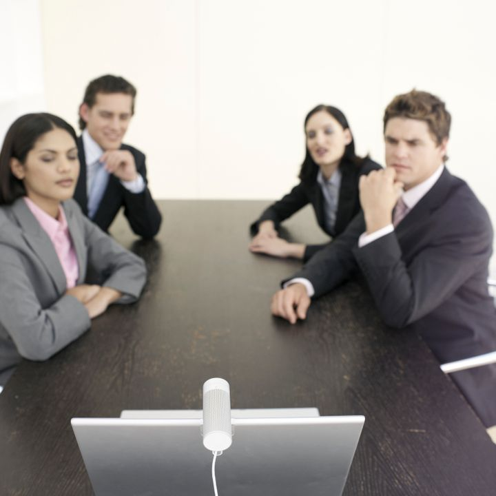 Four business people sitting at desk having video conference (focus on foreground)