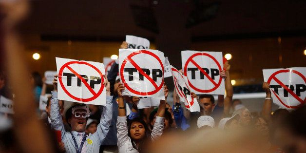 Alternate delegates protesting against the Trans Pacific Partnership (TPP) hold up signs during the first sesssion at the Dem