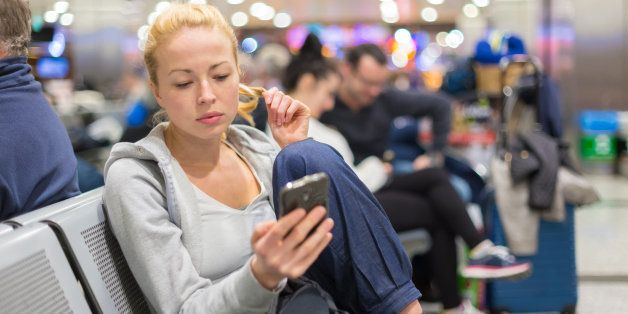 Casual blond young woman using her cell phone while waiting to board a plane at the departure gates. Wireless network hotspot