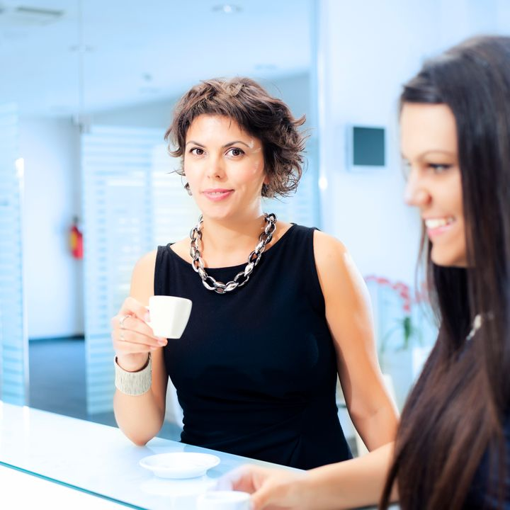 Two young female executives having a friendly discussion over coffee