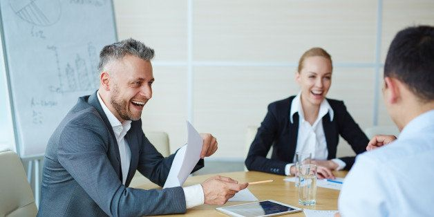 Laughing businessman with paper talking to colleagues in office