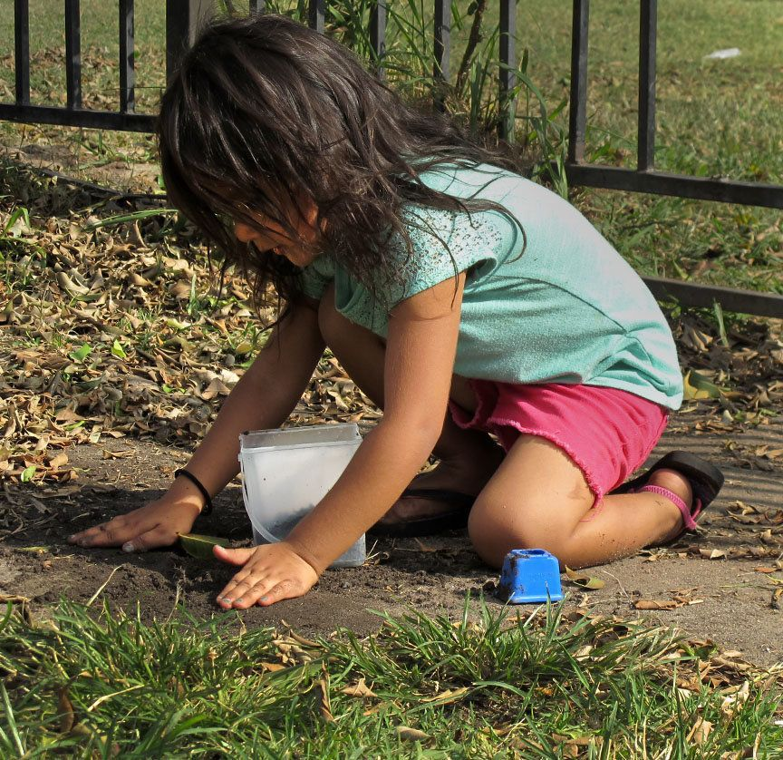 A child plays with dirt in the yard of a Townsend Street apartment complex where tests show the soil contains low levels of l