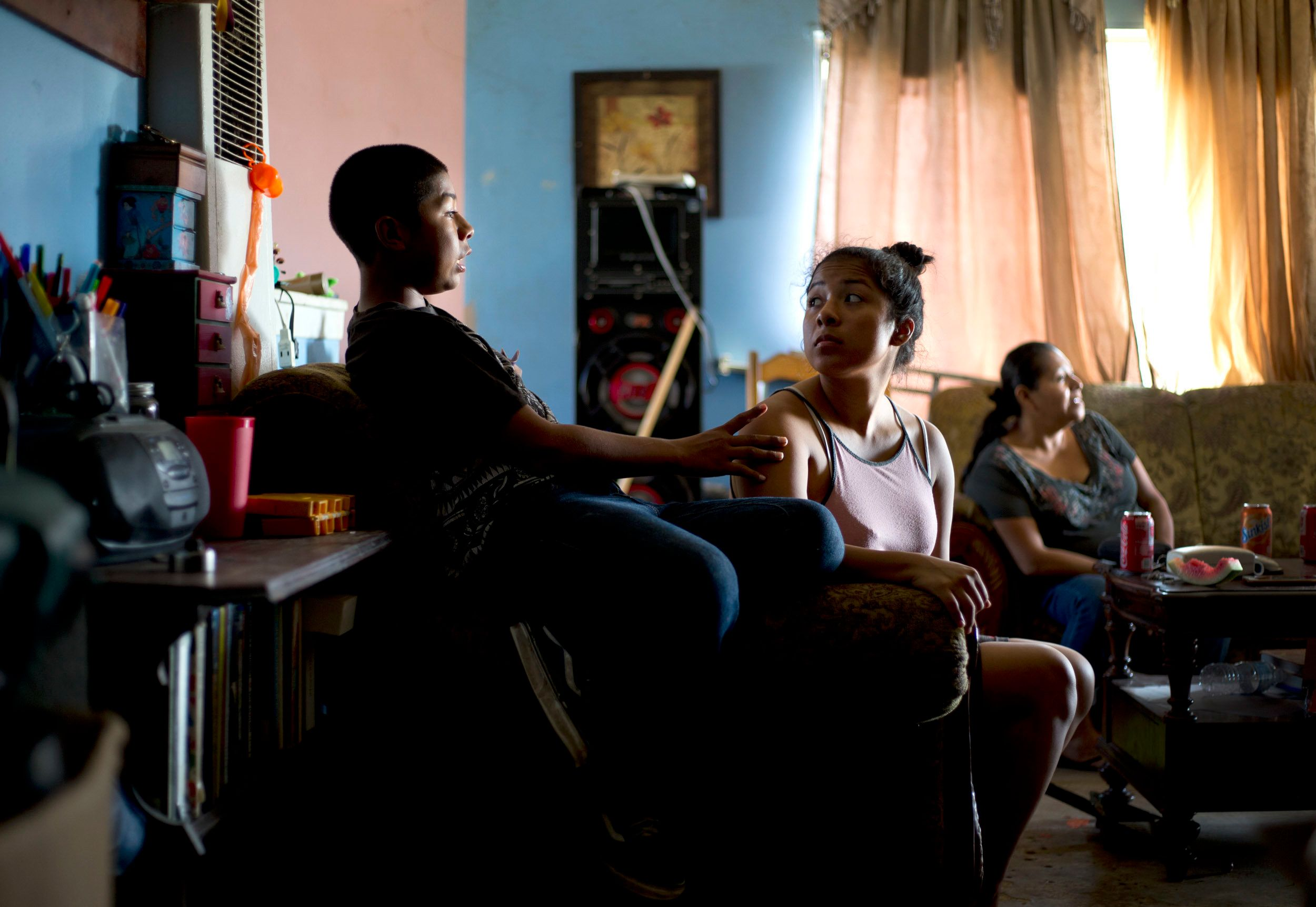 Cesar (left) with his sister Nadia, 18, and mother, Kenia (right), in the living room of their Townsend Street apartment in S