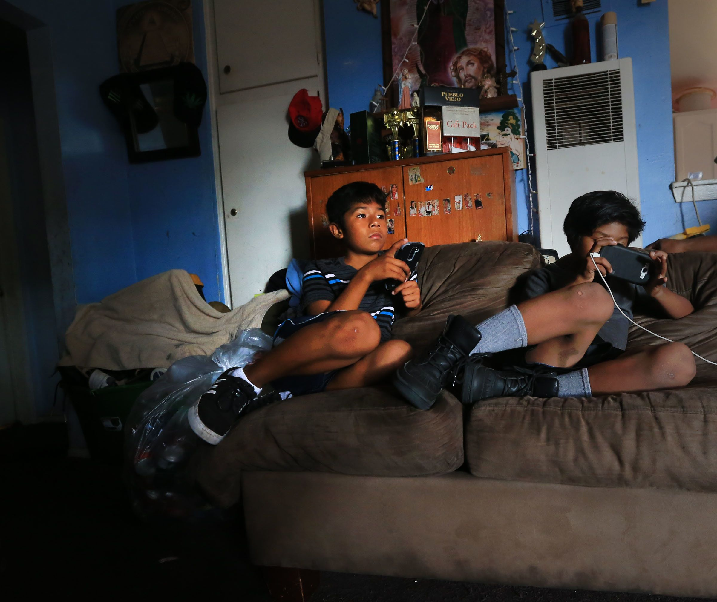 In September 2016, Cesar (left), 11, and his younger brother, Peter, 8, play games on their mobile phones in their Santa Ana