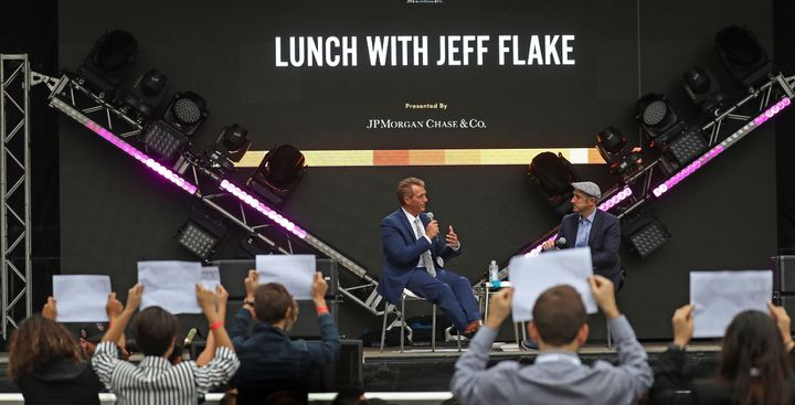 Sen. Jeff Flake (R-Ariz.) talks with the moderator at the Forbes Under 30 Summit in Boston on Monday as anti-Kavanaugh protes