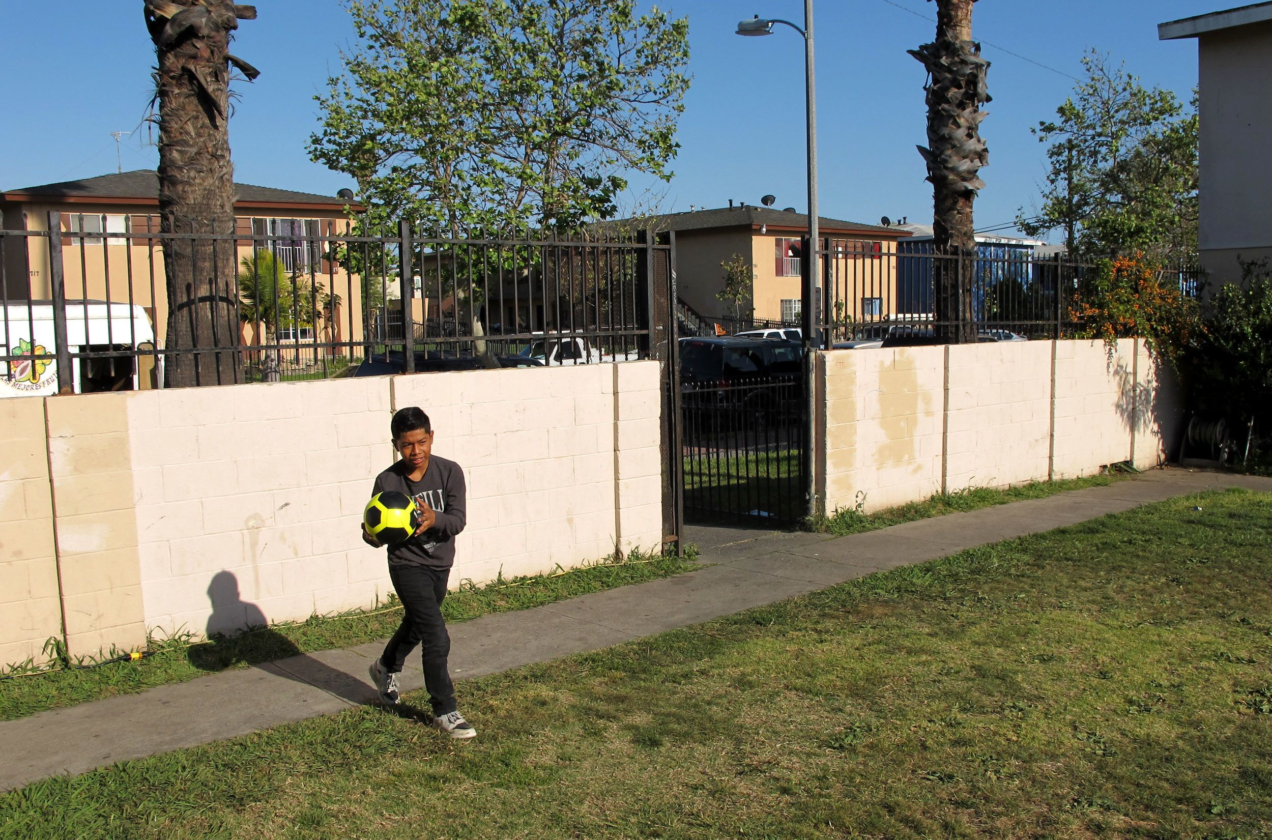 Cesar, 12, plays soccer with his younger brother, Peter (not pictured), in the yard of their Santa Ana apartment complex in A