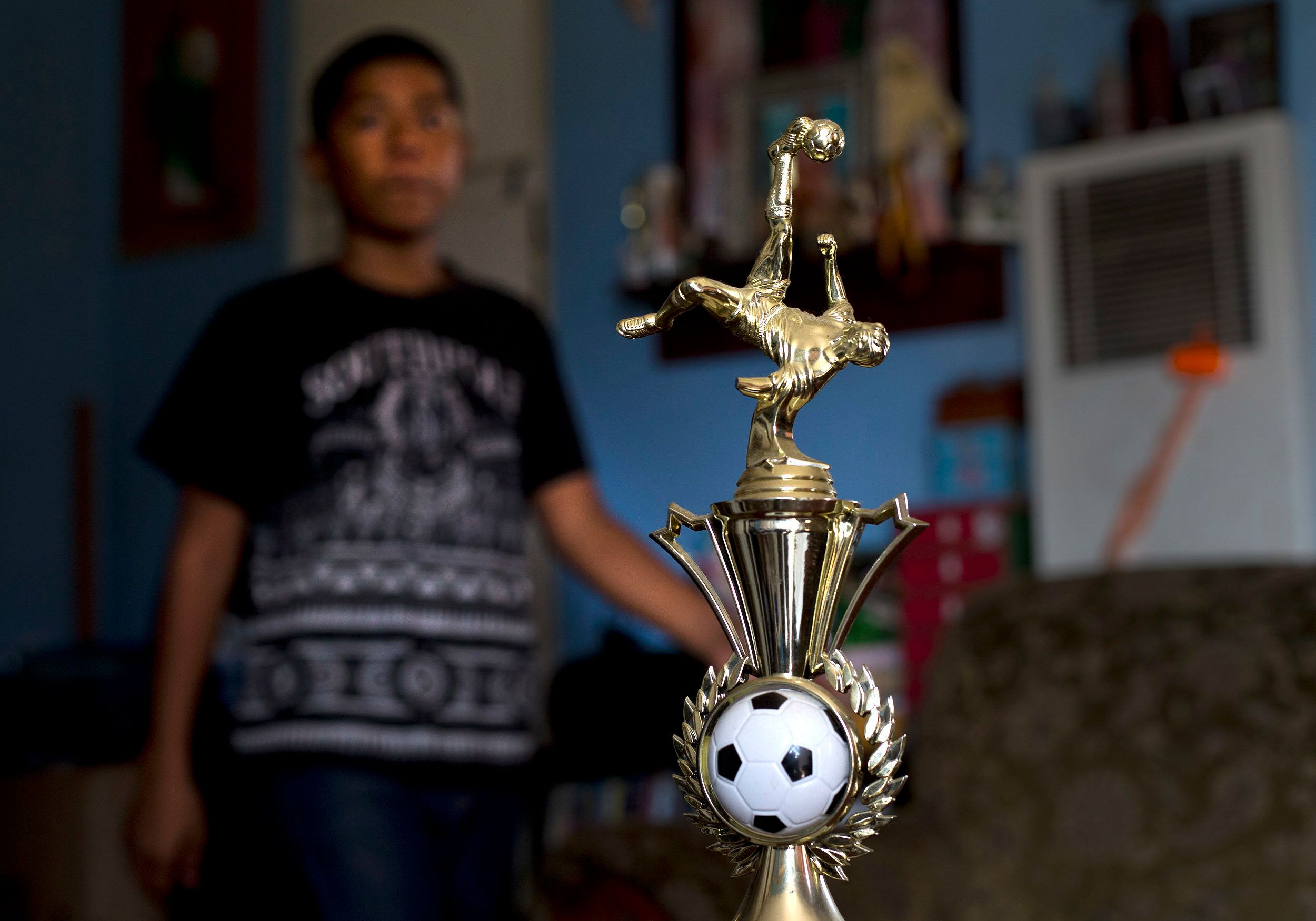 In August 2018, Cesar, 13, walks past the championship trophy he and his soccer team won.