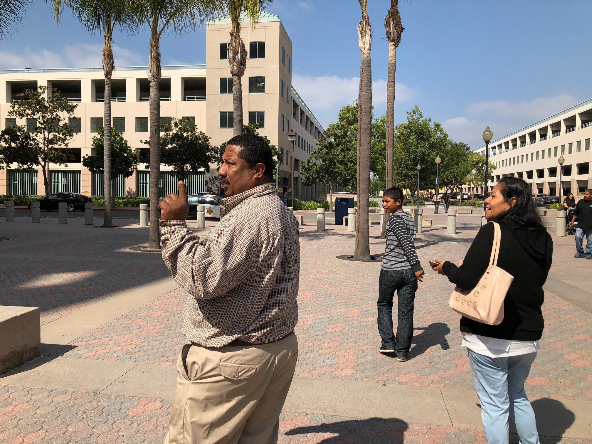 Cesar Gaspar Sr. (left), his wife, Kenia (right), and their son, Cesar (center), leave the Lamoreaux Justice Center in Orange