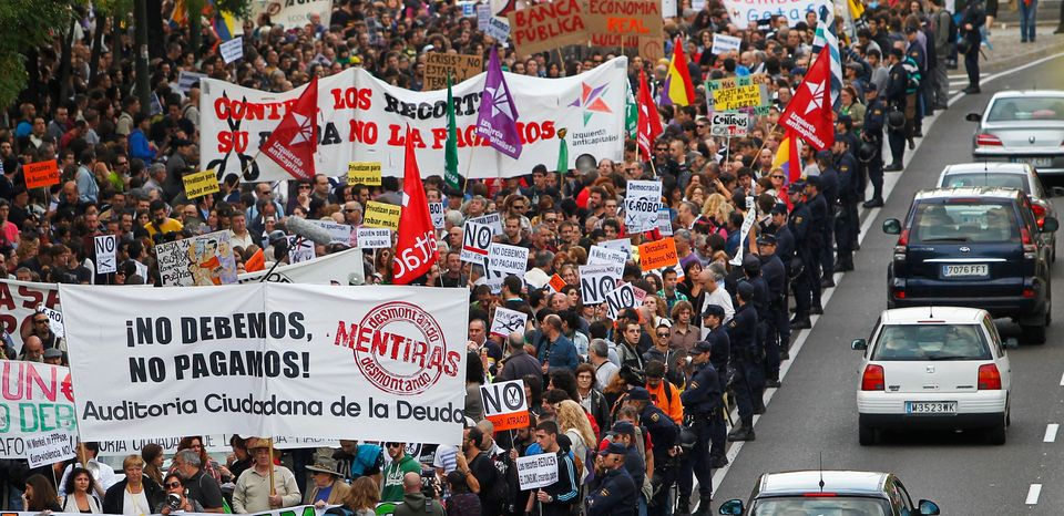 "Protestor march as they hold banners reading ""We don't owe, we won't pay"" against austerity measures announced by the Spanish"