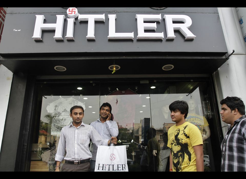 An unidentified customer, left shows a shopping bag as Rajesh Shah, second left and Manish Chandani, second right, the owners