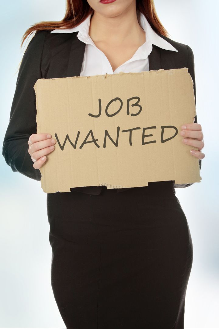 Unemployed businesswoman with cardboard sign - job wanted.