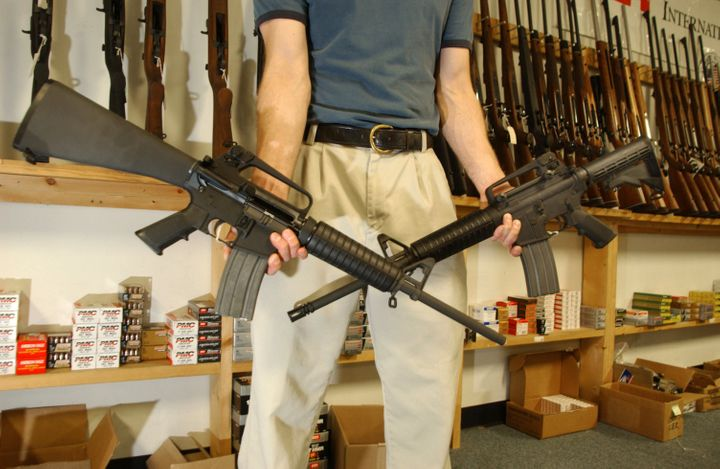 DENVER - SEPTEMBER 13:  The Manager of Dave's Guns holds two Colt AR-15's, the gun on the right has a bayonet mount, flash su