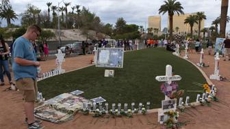 Oct 1, 2018; Las Vegas, NV, USA; People gather at a memorial set up next to the 'Welcome to Las Vegas' sign as Las Vegas remembers the mass shooting at the Route 91 Harvest Festival one year later. Mandatory Credit: Jason Bean/Reno Gazette-Journal via USA TODAY NETWORK/Sipa USA *** NO TABLOIDS ***