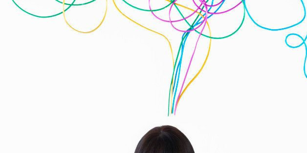 woman smiling with jumbled colored wire above head