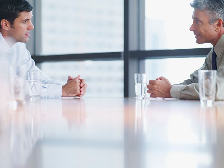 Two businessmen in boardroom with paperwork