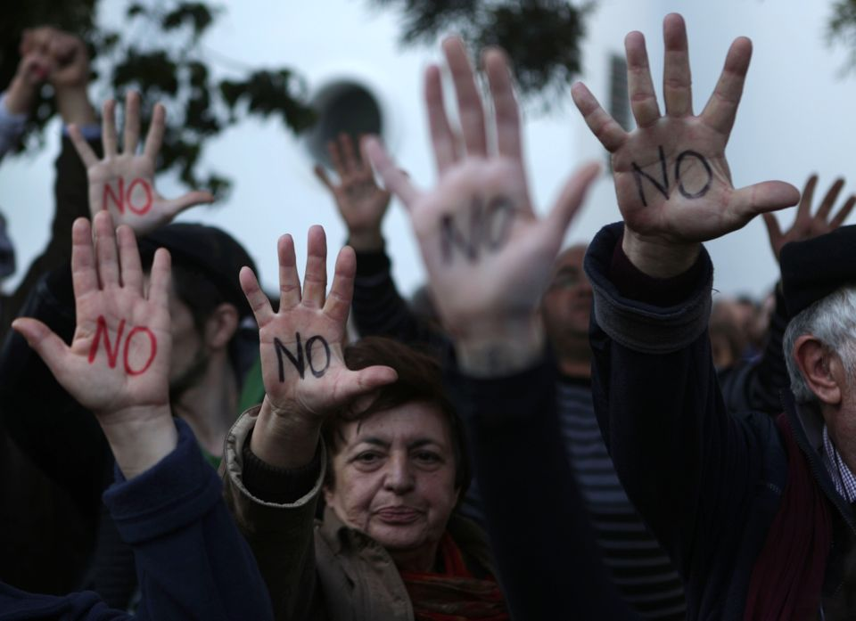 Cypriots show their palms reading 'No' during a protest against an EU bailout deal outside the parliament in Nicosia on March