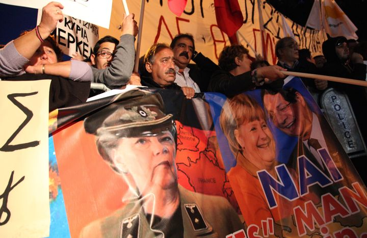Cypriot protestors wave banners picturing German Chancellor Angela Merkel (C) and Cypriot President Nicos Anastasiades (R) du