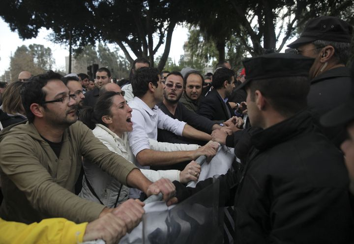 Employees of Cyprus' Laiki (Popular) Bank protest outside the parliament building in the capital Nicosia on March 22, 2013, a
